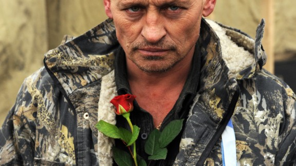 A man brings a rose to a memorial to the anti-government protesters killed durign the past weeks' clashes with riot police in Kiev's Independence Square on February 23, 2014.