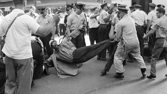 """Chicago police drag away one of 80 civil-rights marchers who were arrested after staging a rush hour sit-in on a downtown street in Chicago on June 28, 1965. Leaders of the march, dissatisfied with results of a two-hour meeting with the mayor, ordered marchers to assume """"arrest position."""""""