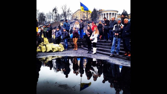KIEV, UKRAINE:  Ukrainians are reflected in a puddle as they gather to mourn the dead in Maidan Square on February 23, after protesters succeeded in forcing President Viktor Yanukovich out of office.  Photo by CNN's Christian Streib.  Follow Christian on Instagram at instagram.com/christianstreibcnn.