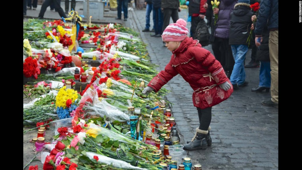 KIEV, UKRAINE:  A young girl pays tribute to anti-government protesters killed in the clashes with riot police by placing a flower on a makeshift memorial leading to the barricades in central Kiev on February 24.  Photo by CNN's Todd Baxter.