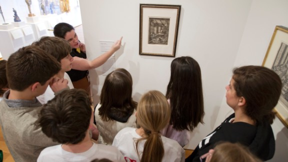 """Christina Westpheling, the teen programs assistant at the High Museum of Art, speaks to a group of sixth grade students about the <a href=""""https://www.high.org/Art/Exhibitions/Paper-and-Ink.aspx"""" target=""""_blank"""" target=""""_blank"""">""""Paper and Ink""""</a> exhibit, which allowed students to look inside the practice of printmaking."""