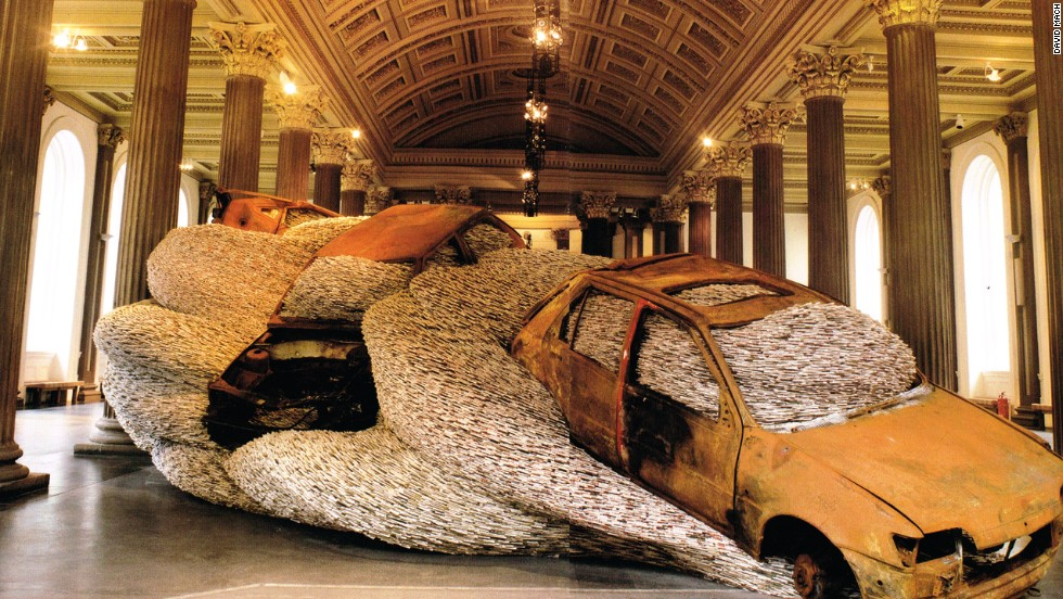 "A work titled ""Bangers 'N' Mash"" on display in Glasgow depicts wrecked cars filled with magazines."