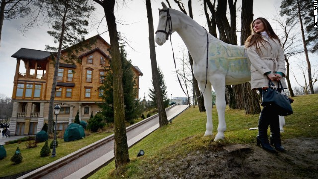 A woman stands near a sculpture of a horse around President Viktor Yanukovych's Mezhyhirya estate, which was abandoned by security, on February 26, 2014 in Kiev, Ukraine.