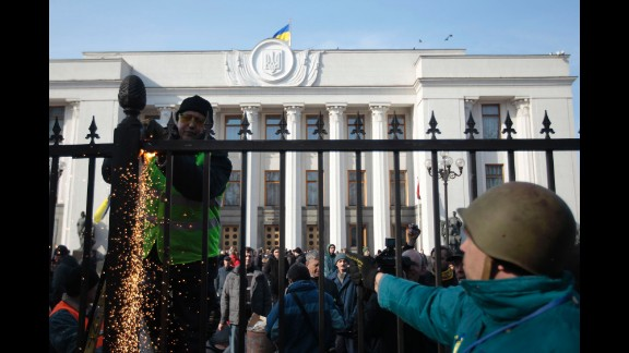 Protesters remove a fence that surrounds Ukraine