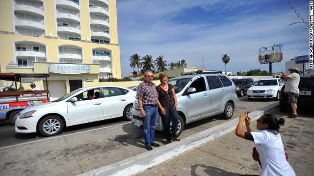 A couple poses for a photo in front of the Miramar condominium in Mazatlan, State of Sinaloa, Mexico on February 22, 2014, where Mexican drug trafficker Joaquin Guzman Loera aka 'el Chapo Guzman' was arrested early this morning by Mexican marines. Guzman is the Sinaloa cartel leader and the most wanted by US and Mexican anti-drug agencies. AFP PHOTO/Fernando Brito (Photo credit should read Fernando Brito/AFP/Getty Images)