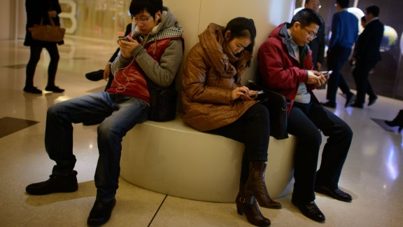 In a photo taken on November 27, 2013 people use their mobile phones as they sit inside a shopping mall in Beijing. China's new free-trade zone has drawn just 38 overseas firms in its first two months of operations, officials said, as foreign companies await concrete policies and deeper reforms. AFP PHOTO / Ed Jones (Photo credit should read ED JONES/AFP/Getty Images)