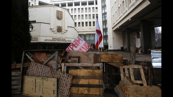"Barricades in front of a government building in Simferopol on February 27 hold a banner that reads: ""Crimea Russia."" There"