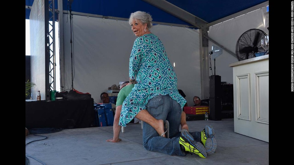 Paula Deen rides fellow celebrity chef Robert Irvine during the South Beach Wine & Food Festival on Sunday, February 23, in Miami Beach, Florida.