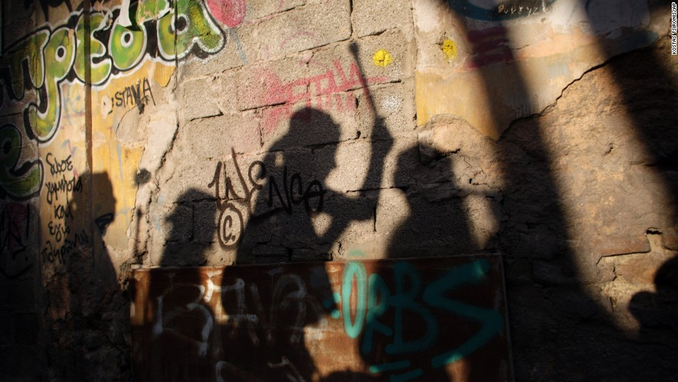 Musicians playing drums cast their shadows on a graffiti-painted wall as they perform during a carnival celebration in Athens, Greece, on Sunday, February 23.