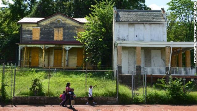A boarded-up house sits blocks from the Anacostia Playhouse, in a Washington neighborhood undergoing gentrification.