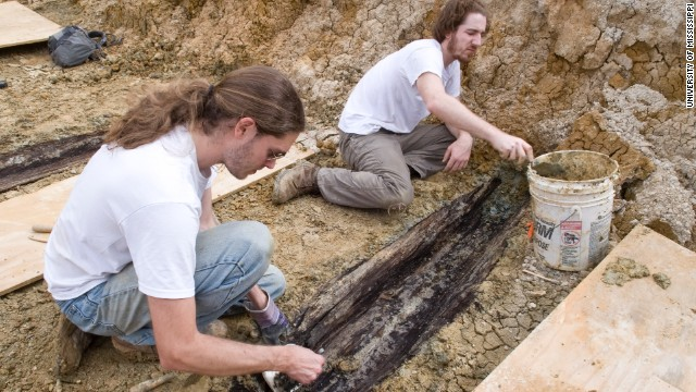 Derek Anderson and Forrest Follett remove the soil from the lid of one the graves.