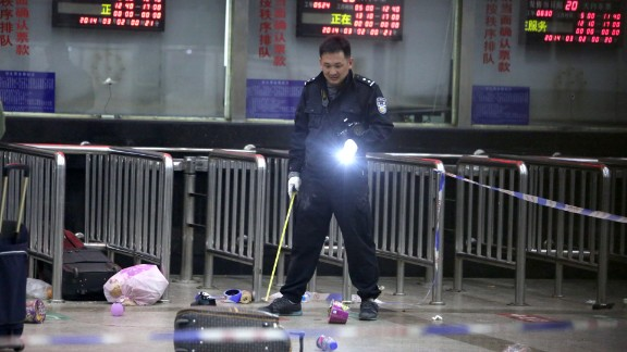 A Chinese police investigator inspects the scene of the attack at the railway station on March 2, 2014.