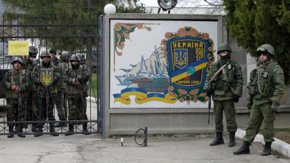 Ukrainian soldiers, left, and unidentified gunmen, right, stand at the gate of an infantry base in Perevalne on March 2.