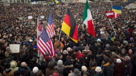 Protesters hold flags of the United States, Germany and Italy during a rally in Independence Square on March 2.