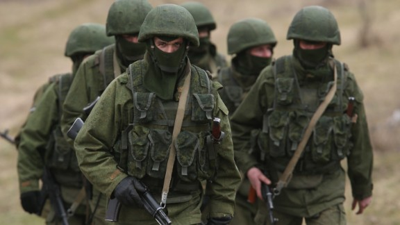 Soldiers who were among several hundred that took up positions around a Ukrainian military base walk on the base