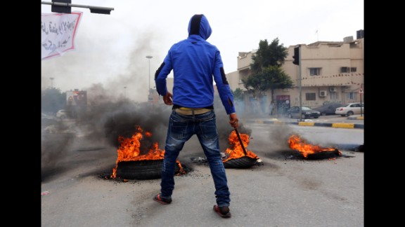 A protester sets tires on fire outside of the Libyan General National Congress in Tripoli on Sunday.