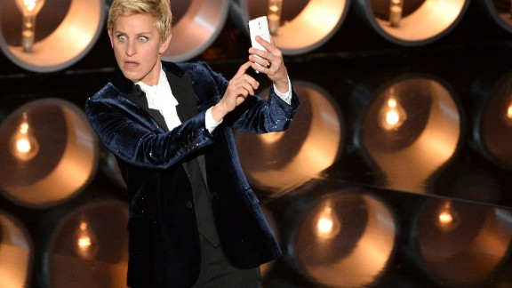 """DeGeneres <a href=""""https://twitter.com/TheEllenShow/status/440302561044594688"""" target=""""_blank"""" target=""""_blank"""">takes a selfie</a> on stage near the start of the show."""