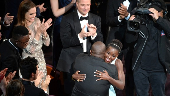 """Nyong'o hugs """"12 Years a Slave"""" director Steve McQueen after winning the best supporting actress Oscar."""
