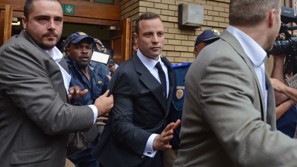 Pistorius is escorted out of the court Monday, March 3, after the first day of his murder trial.