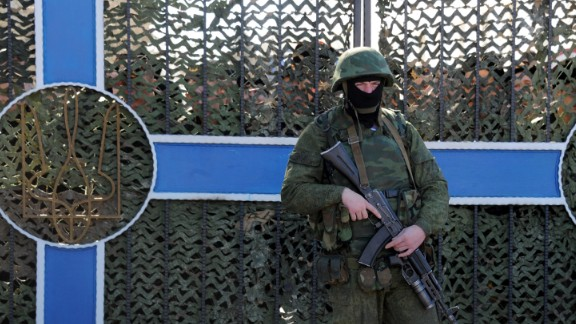 Ukrainian soldier stands behind a fence while unidentified armed men block the headquarters of the Ukrainian Navy in Sevastopol on March 3, 2014. The Russian Black Sea Fleet commander Aleksandr Vitko has issued an ultimatum to the Ukrainian military personnel in Crimea, the Interfax-Ukraine news agency reported. Ukraine accused Russia on Monday of pouring more troops into Crimea as world leaders grappled with Europe