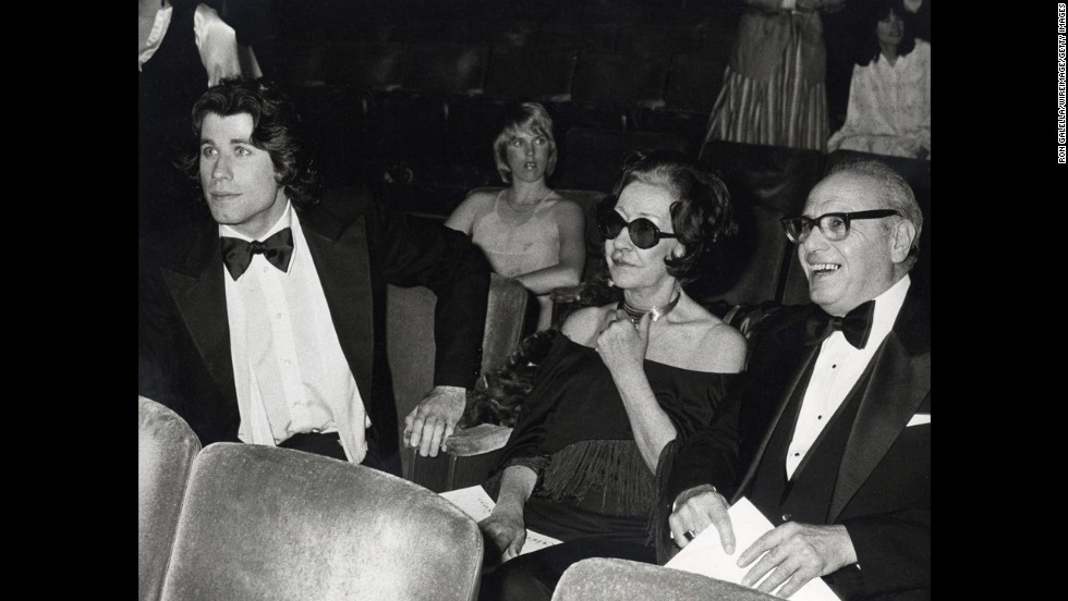 John Travolta, left, sits with his parents, Salvatore Travolta, right, and Helen Cecilia Burke Travolta, center, during the 50th Annual Academy Awards at Dorothy Chandler Pavilion in Los Angeles, California.