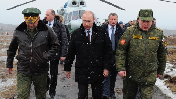 Russian President Vladimir Putin, center, and Defense Minister Sergei Shoigu, left, and the commander of the Western Military District Anatoly Sidorov, right, walk upon arrival to watch military exercise near St.Petersburg, Russia, Monday, March 3, 2014. Putin has sought and quickly got the Russian parliament