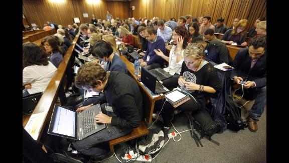 Members of the media work during a break in proceedings March 4.