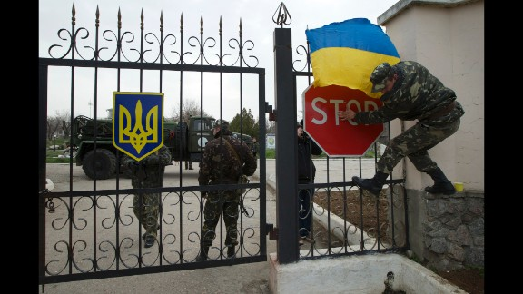 A Ukrainian airman puts the Ukrainian national flag over the gate of the Belbek air base as they guard what