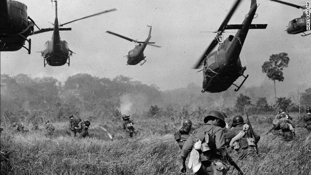FILE - In this March 1965 file photo shot by Associated Press photographer Horst Faas, hovering U.S. Army helicopters pour machine gun fire into the tree line to cover the advance of South Vietnamese ground troops in an attack on a Viet Cong camp 18 miles north of Tay Ninh, Vietnam, northwest of Saigon near the Cambodian border.  (AP Photo/Horst Faas, File)