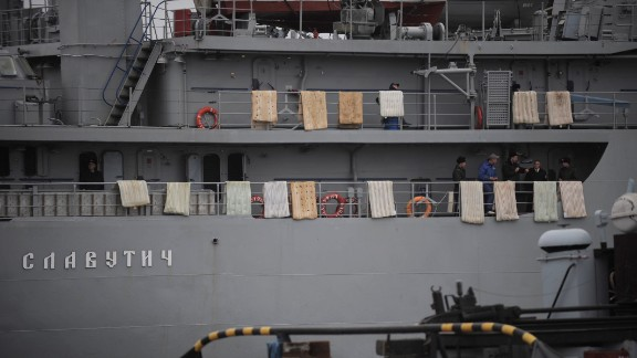 People stand on the Ukrainian Navy ship Slavutych while it