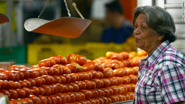 A woman buys tomatoes at a popular market in Caracas on October 24, 2013.