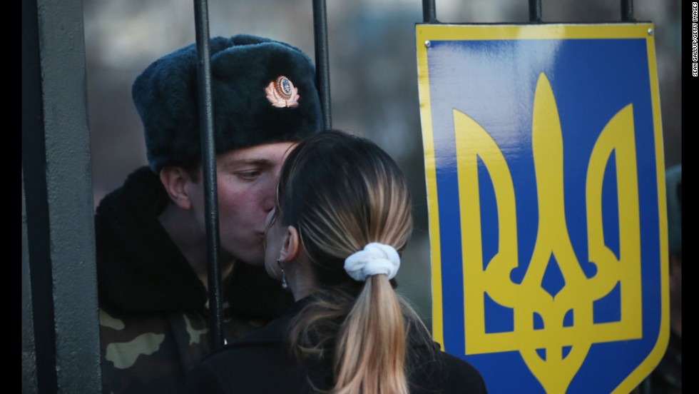Oleg, a Ukrainian soldier, kisses his girlfriend, Svetlana, through the gates of the Belbek air base entrance near Sevastopol, Ukraine, on Monday, March 3.