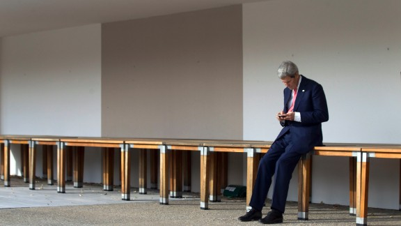 Kerry checks his cell phone in Geneva, Switzerland, prior to a November 2103 meeting with Iran