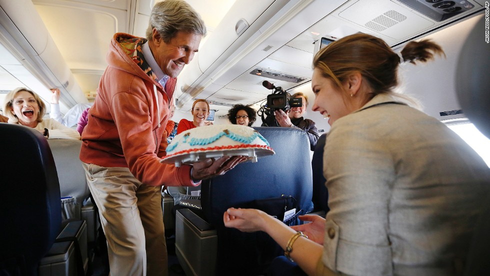 During a flight from Kabul, Afghanistan, to Paris in March 2013, Kerry presents a birthday cake to traveling CBS correspondent Margaret Brennan.