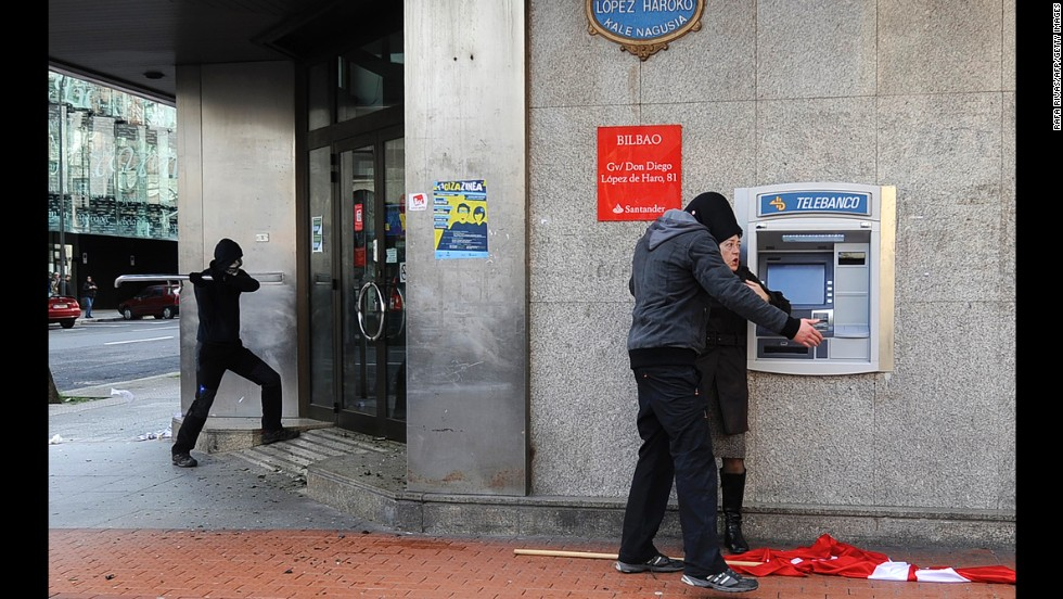 A masked demonstrator attacks a bank office in Bilbao, Spain, to protest the Global Forum Spain on Monday, March 3.