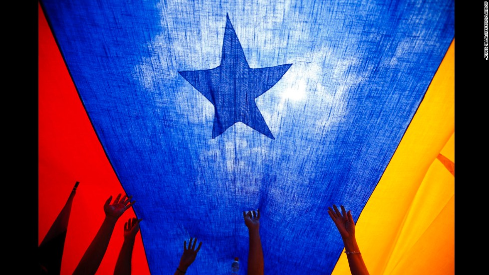 Anti-government protesters stand under a flag during a rally in Caracas, Venezuela, on Sunday, March 2.