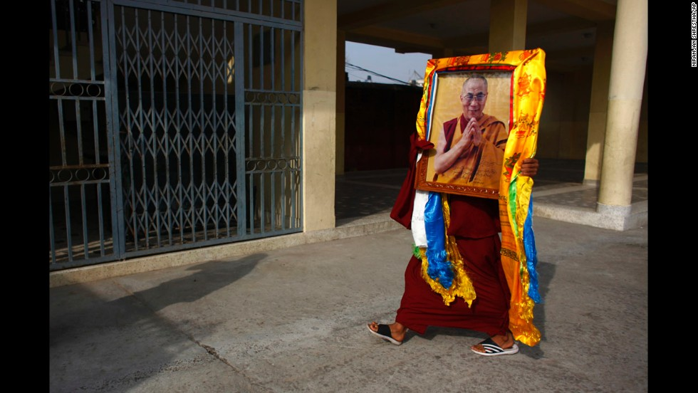 A Tibetan monk in Kathmandu, Nepal, carries a portrait of the Dalai Lama during festivities marking the last day of the Tibetan New Year, or Losar, on Tuesday, March 4.