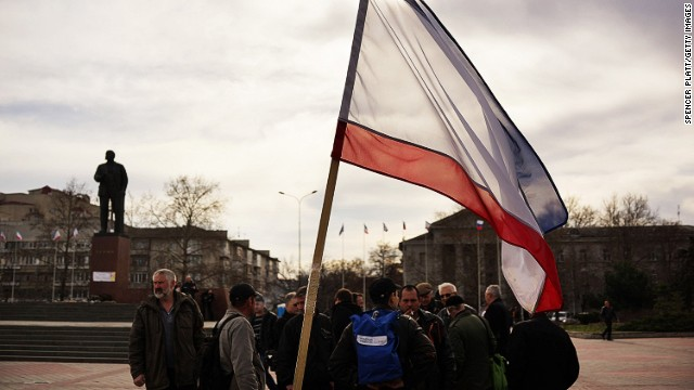 Members of a pro Russian volunteer force gather in formation next to a statue of Lenin and the Crimean flag on March 6, 2014 in Simferopol, Ukraine.