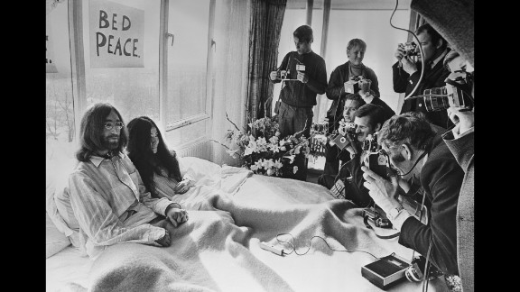 """John Lennon and Yoko Ono pose for the press at their hotel in Amsterdam, Netherlands, in March 1969. The couple stayed in bed for seven days """"as a protest against war and violence in the world."""""""