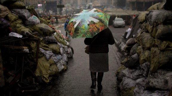 A woman walks past barricades March 6 that were set up by anti-government protesters in Kiev