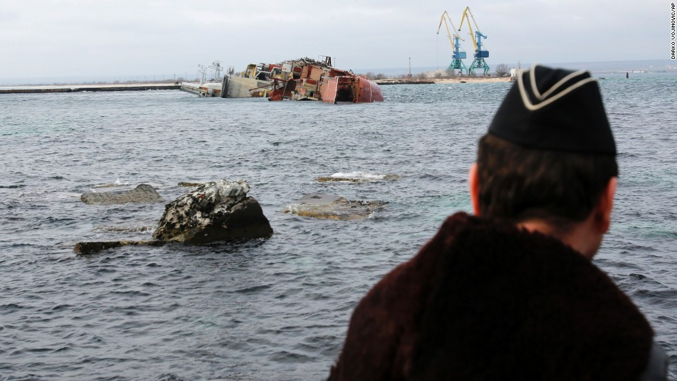 A Ukrainian navy officer looks at the scuttled, decommissioned Russian vessel Ochakov from the Black Sea shore outside the town of Myrnyi, Ukraine, on March 6. Russian naval personnel scuttled the ship, blockading access for five Ukrainian naval vessels.