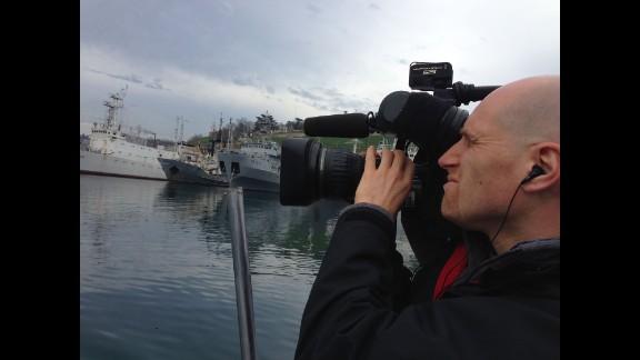 SEVASTOPOL, UKRAINE:  Cameraman Chris Jackson captures the Russian Black Sea fleet in Sevastopol on March 5.  Photo by CNN's Ben Wedeman.  Follow Ben on Instagram at instagram.com/bcwedeman.