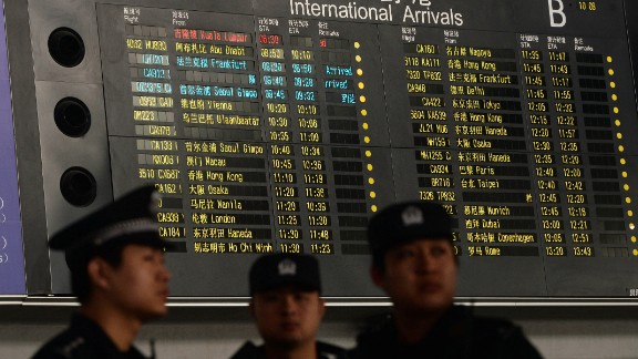 Chinese police at the Beijing airport stand beside the arrival board showing delayed Flight 370 in red on March 8, 2014.