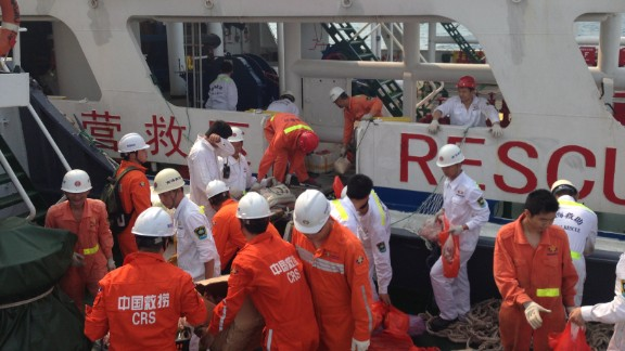 Members of a Chinese emergency response team board a rescue vessel at the port of Sanya in China
