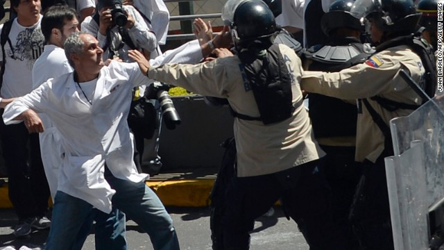 Venezuelan public health workers scuffle with riot police during a protest in Caracas on March 10, 2014. At least 20 people have died and 300 others wounded since protests first erupted, giving President nicolas Maduro his biggest test since succeeding late leader and leftist icon Hugo Chavez almost a year ago. AFP PHOTO/JUAN BARRETO (Photo credit should read JUAN BARRETO/AFP/Getty Images)