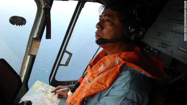 This picture taken aboard a Vietnamese Air Force Russian-made MI-171 helicopter shows a crew member in the cockpit during a search flight some 200 km over the southern Vietnamese waters off Vietnam's island Phu Quoc on March 11, 2014 as part of continued efforts aimed at finding traces of the missing Malaysia Airlines MH370.