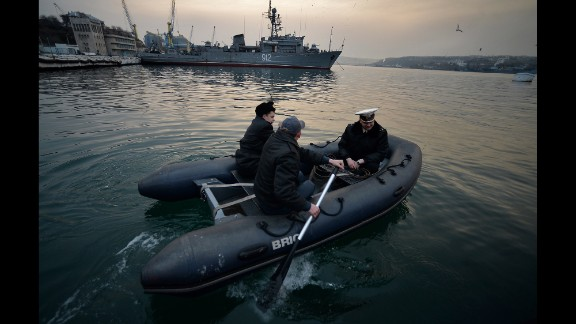 Ukrainian naval officers board a boat in front of the Russian minesweeper Turbinist in Sevastopol