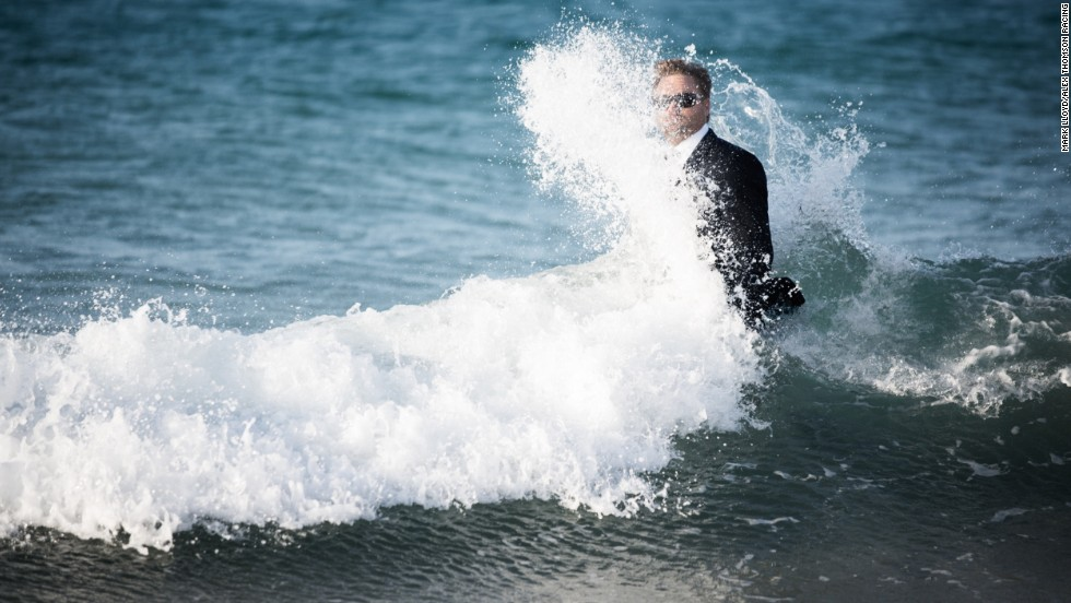Waves crash against Thomson, bedecked in only a water-resistant designer suit, which is worn for the entire stunt, as he returns to shore.