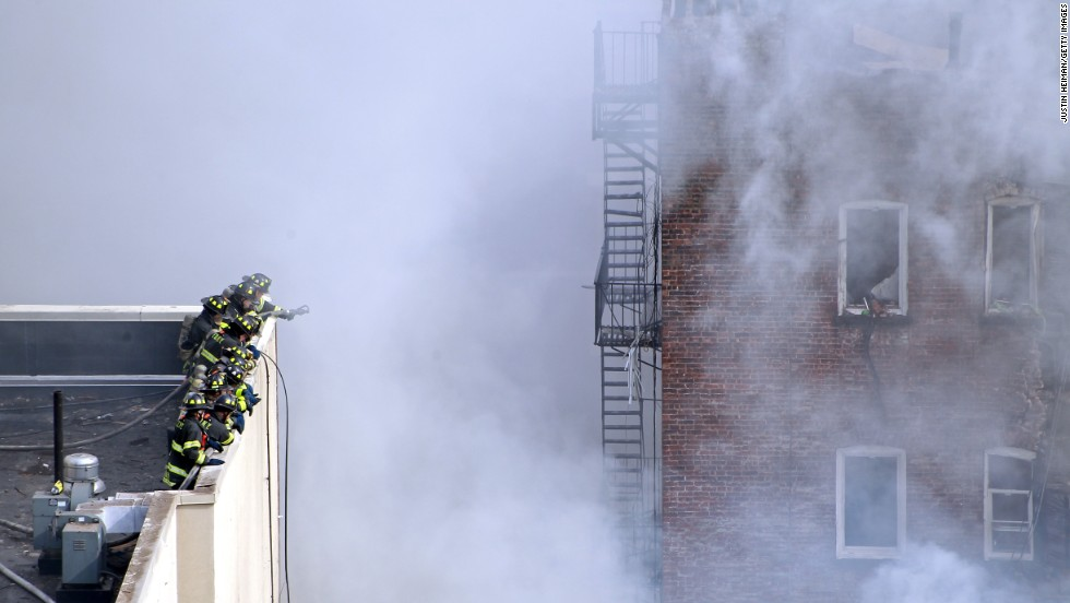 Firefighters work from the roof of a building next to the site of the explosion.