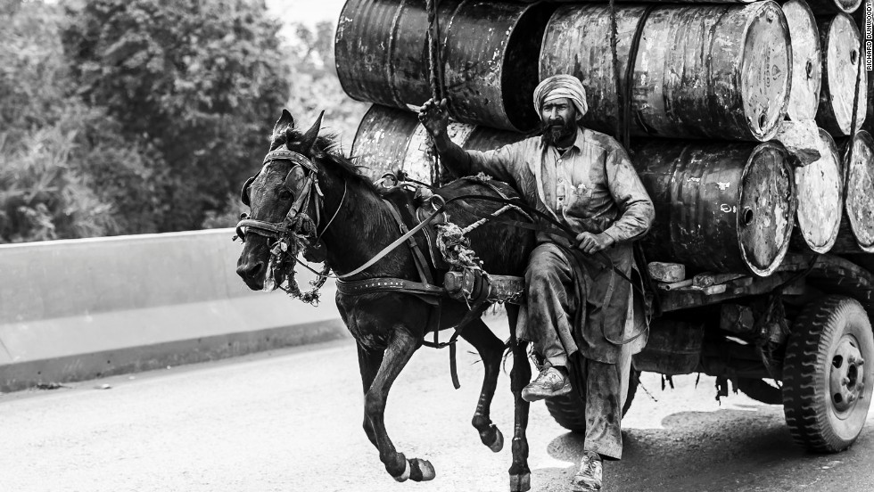 A man drives his horse at full tilt down a dual carriageway with a large load of empty water barrels in Faisalabad, Pakistan.